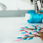 Picture of workspace in the embroidery machine close up look under the needle, lovely tree minimal sytle on background have two colorfull thread cyan and pink.